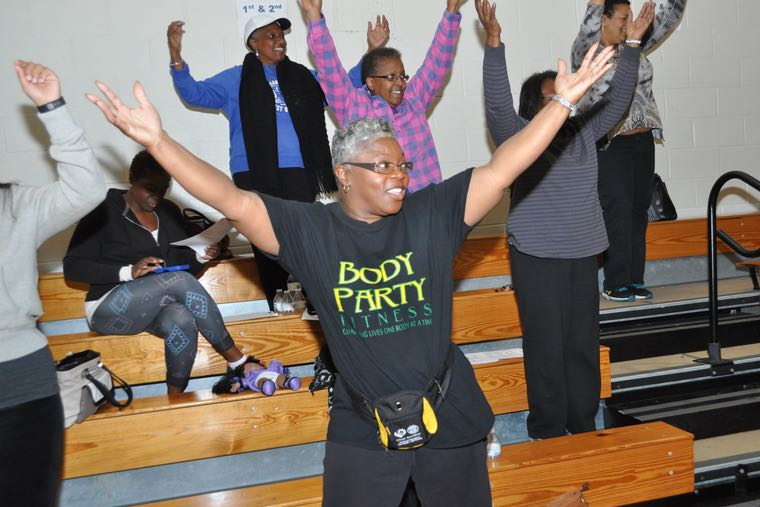 As she waits for her health screening, Patricia Williams of New Life Fellowship Church takes part in an impromptu workout session in the gymnasium at First Baptist Church-West. (Photo: Qcitymetro.com