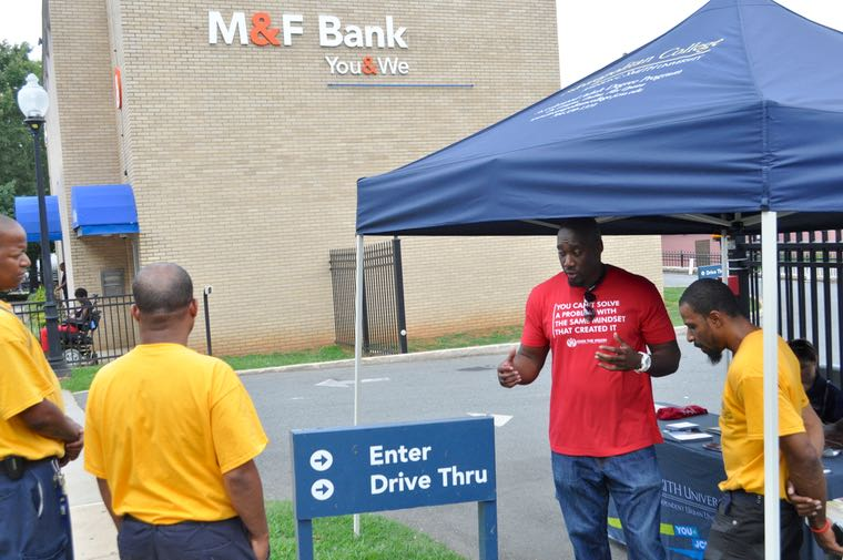 At the Mechanics & Farmers Bank on Beatties Ford Road, community activist Jason L. Warner, third from left, talks with passersby about the national Bank Black campaign. (Photo: Qcitymetro.com)