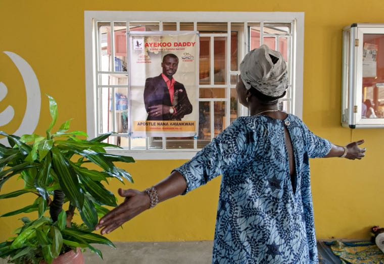 A woman prays in front of a poster of the leader of Power Breakers International Ministries Accra, Ghana December 4, 2016. REUTERS/Francis Kokoroko